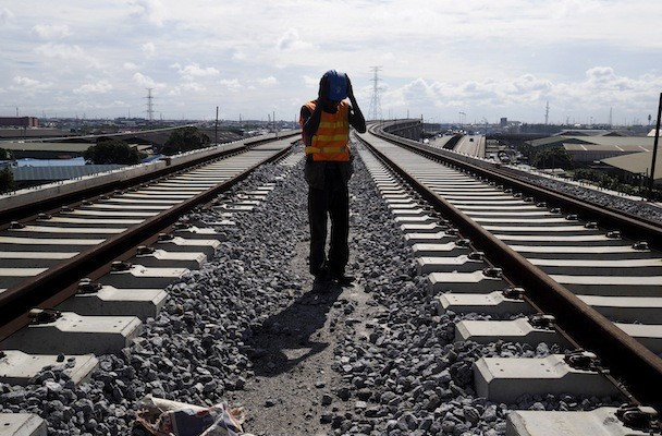 A worker adjusts his hard hat at the National Arts Theatre stop of the light rail system under construction in Lagos